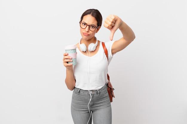 Jovem mulher hispânica se sentindo mal, mostrando os polegares para baixo. conceito de estudante