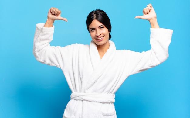 Jovem mulher hispânica se sentindo orgulhosa, arrogante e confiante, parecendo satisfeita e bem-sucedida, apontando para si mesma. conceito de roupão de banho