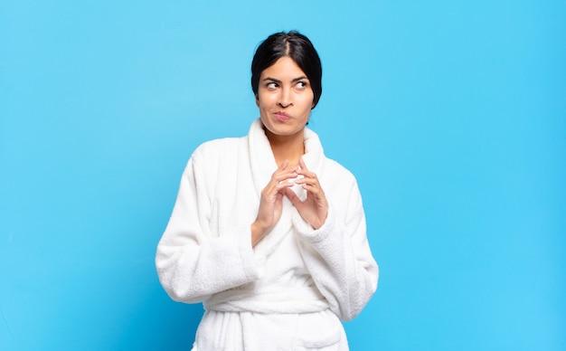 Jovem mulher hispânica se sentindo orgulhosa, travessa e arrogante enquanto trama um plano maligno ou pensa em um truque. conceito de roupão de banho