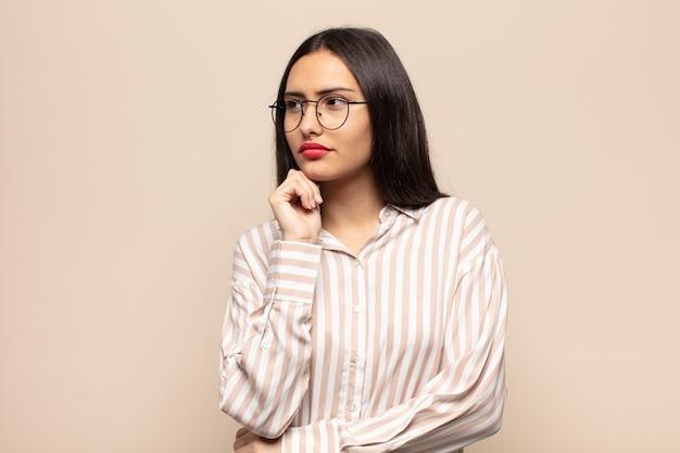 Jovem mulher hispânica se sentindo pensativa, imaginando ou imaginando ideias, sonhando acordada e olhando para cima para copiar o espaço