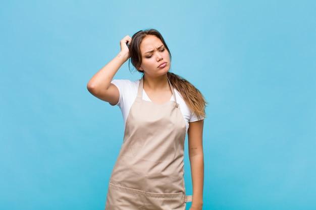 Jovem mulher hispânica se sentindo perplexa e confusa, coçando a cabeça e olhando para o lado