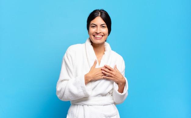 Jovem mulher hispânica se sentindo romântica, feliz e apaixonada, sorrindo alegremente e segurando o coração de mãos dadas