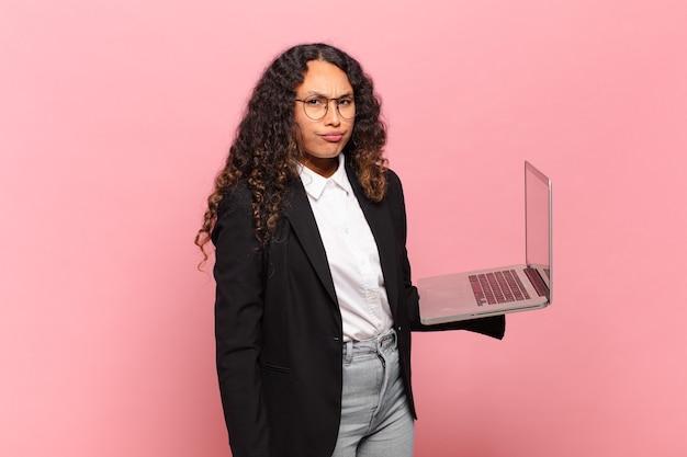 Jovem mulher hispânica se sentindo triste, chateada ou com raiva e olhando para o lado com uma atitude negativa, franzindo a testa em desacordo. conceito de laptop