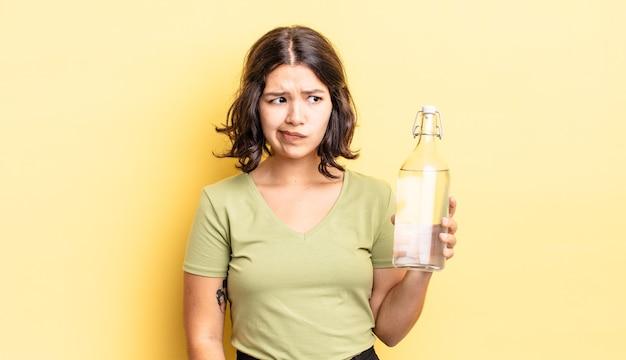 Jovem mulher hispânica se sentindo triste, chateada ou com raiva e olhando para o lado. conceito de garrafa de água