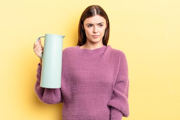 Jovem mulher hispânica se sentindo triste, chateada ou com raiva e olhando para o lado. conceito de garrafa térmica de café
