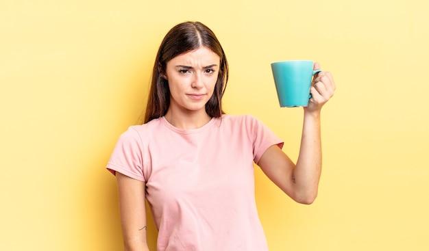 Jovem mulher hispânica se sentindo triste, chateada ou com raiva e olhando para o lado. conceito de xícara de café