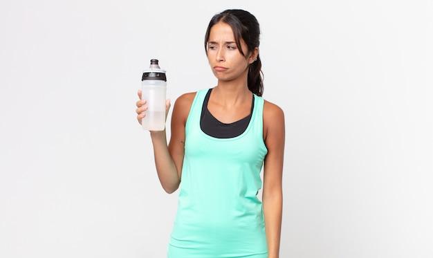 Jovem mulher hispânica se sentindo triste, chateada ou com raiva e olhando para o lado e segurando uma garrafa de água. conceito de fitness