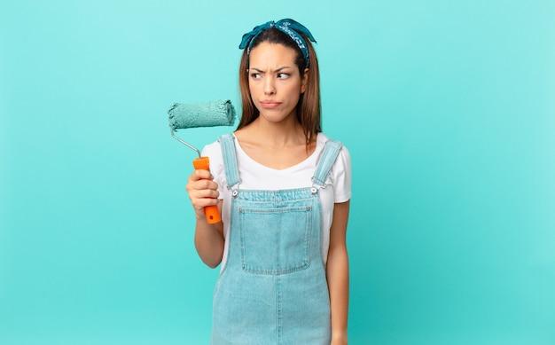 Jovem mulher hispânica se sentindo triste, chateada ou com raiva, olhando para o lado e pintando uma parede