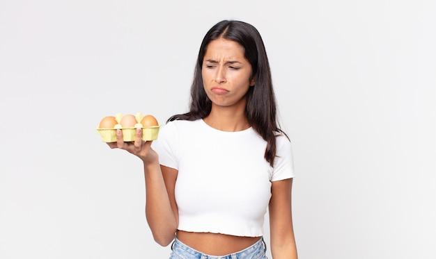 Jovem mulher hispânica se sentindo triste, chateada ou com raiva, olhando para o lado e segurando uma caixa de ovos