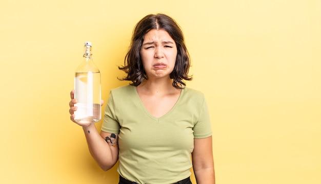 Jovem mulher hispânica se sentindo triste e chorona com um olhar infeliz e chorando. conceito de garrafa de água