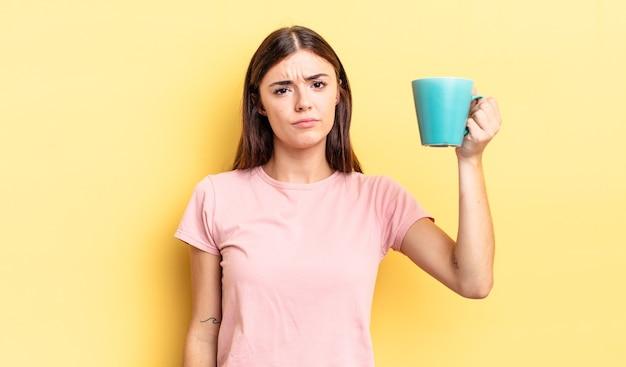 Jovem mulher hispânica se sentindo triste e chorona com um olhar infeliz e chorando. conceito de xícara de café