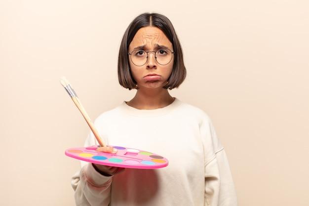 Jovem mulher hispânica se sentindo triste e chorona com uma aparência infeliz, chorando com uma atitude negativa e frustrada