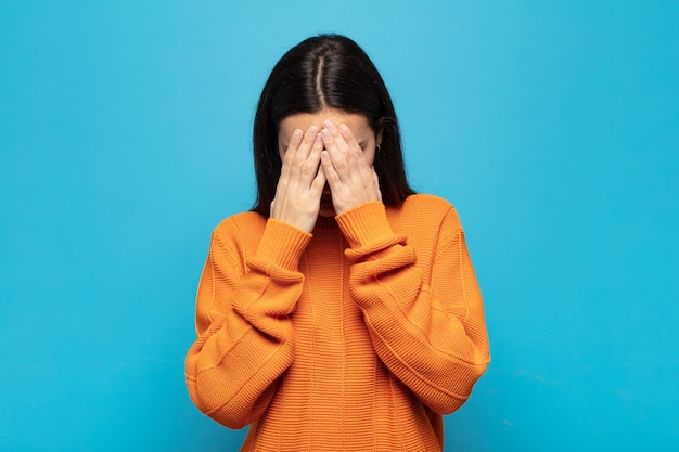 Jovem mulher hispânica se sentindo triste, frustrada, nervosa e deprimida, cobrindo o rosto com as duas mãos, chorando