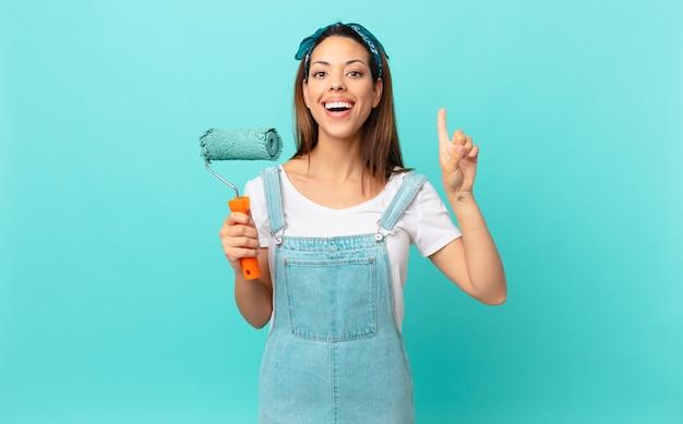 Jovem mulher hispânica se sentindo um gênio feliz e animado depois de perceber uma ideia e pintar uma parede