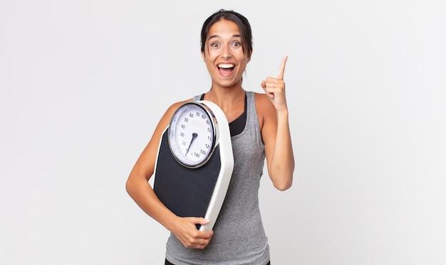 Jovem mulher hispânica se sentindo um gênio feliz e animado depois de perceber uma ideia e segurar uma balança. conceito de dieta