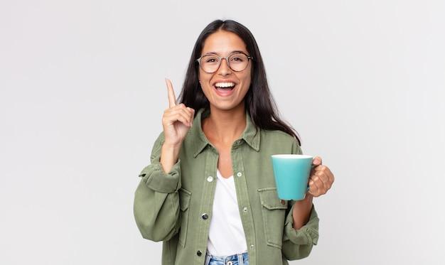 Jovem mulher hispânica se sentindo um gênio feliz e animado depois de perceber uma ideia e segurar uma caneca de café