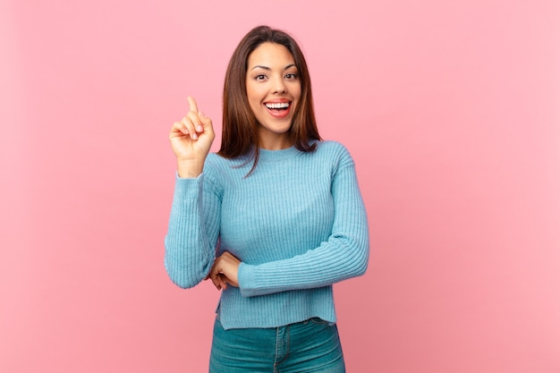 Jovem mulher hispânica se sentindo um gênio feliz e animado depois de realizar uma ideia