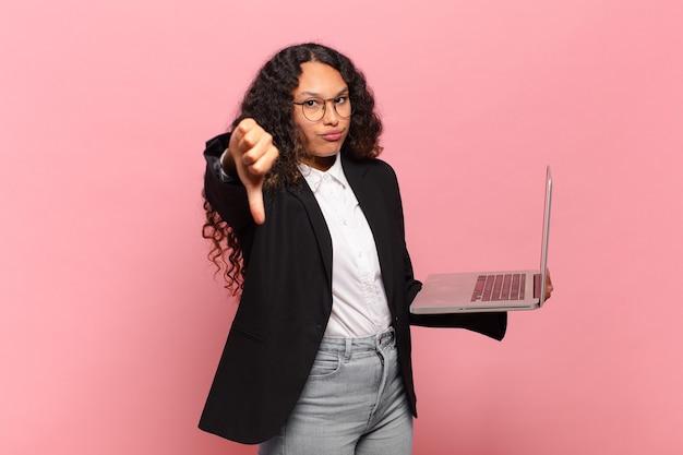 Jovem mulher hispânica se sentindo zangada, irritada, decepcionada ou descontente, mostrando os polegares para baixo com um olhar sério. conceito de laptop