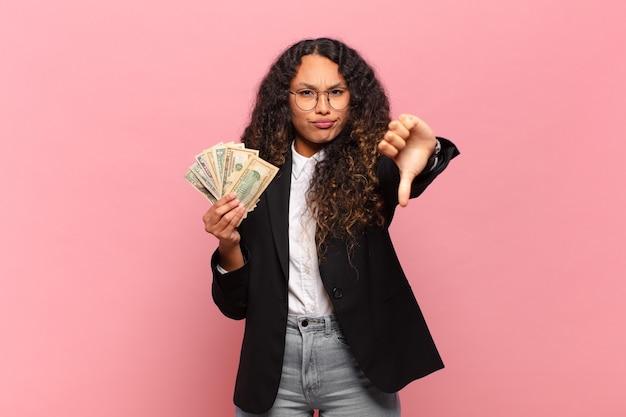 Jovem mulher hispânica se sentindo zangada, irritada, decepcionada ou descontente, mostrando os polegares para baixo com um olhar sério. conceito de notas de dólar