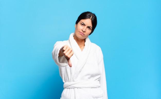 Jovem mulher hispânica se sentindo zangada, irritada, decepcionada ou descontente, mostrando os polegares para baixo com um olhar sério. conceito de roupão de banho