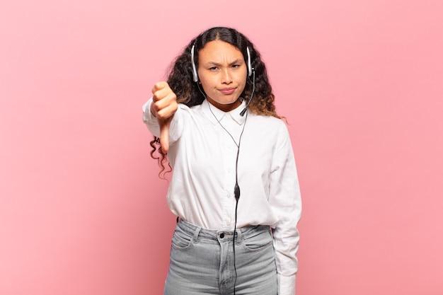Jovem mulher hispânica se sentindo zangada, irritada, decepcionada ou descontente, mostrando os polegares para baixo com um olhar sério. conceito de telemarketing
