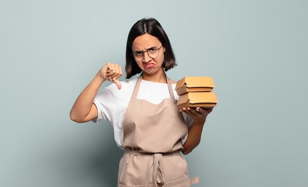 Jovem mulher hispânica se sentindo zangada, irritada, desapontada ou descontente, mostrando o polegar para baixo com um olhar sério