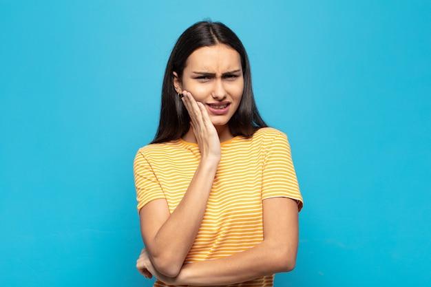 Jovem mulher hispânica segurando a bochecha e sofrendo de dor de dente dolorida, sentindo-se doente, miserável e infeliz, procurando um dentista
