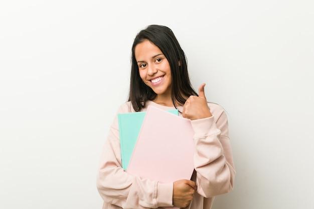Jovem mulher hispânica segurando alguns cadernos sorrindo e levantando o polegar