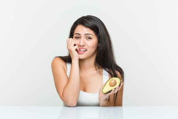 Jovem mulher hispânica, segurando as unhas cortantes de um abacate, nervoso e muito ansioso.