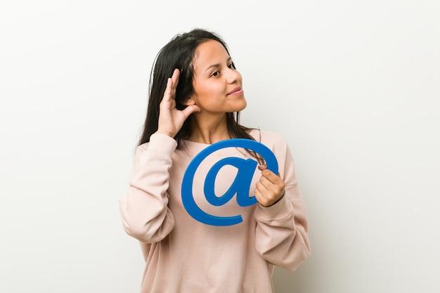 Jovem mulher hispânica segurando no ícone tentando ouvir uma fofoca.