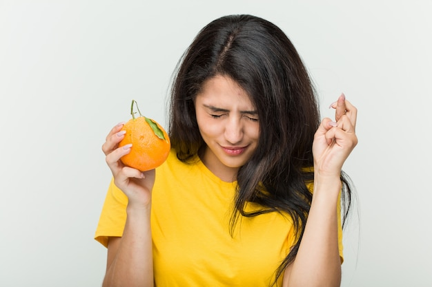 Jovem mulher hispânica, segurando os dedos um cruzamento laranja por ter sorte