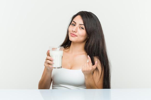 Jovem mulher hispânica, segurando um copo de leite, apontando com o dedo, como se estivesse convidando para se aproximar.