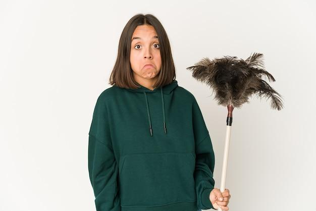 Jovem mulher hispânica segurando um espanador encolhe os ombros e abre os olhos confusos.