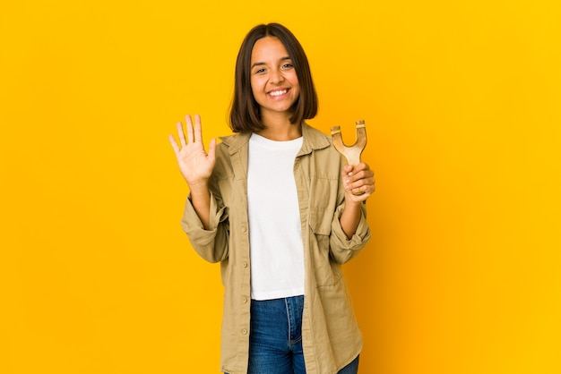 Jovem mulher hispânica segurando um estilingue sorrindo alegre mostrando o número cinco com os dedos.