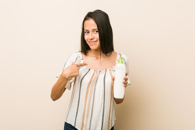 Jovem mulher hispânica, segurando um frasco de creme, apontando com o dedo para você, como se estivesse convidando para se aproximar.