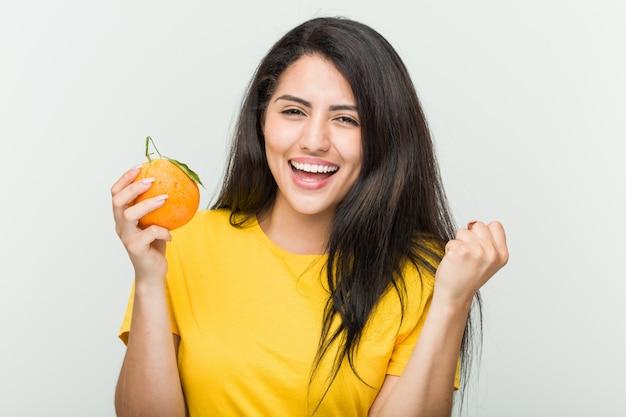Jovem mulher hispânica, segurando um laranja torcendo despreocupado e animado. conceito de vitória