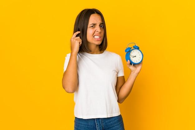 Jovem mulher hispânica segurando um megafone cobrindo as orelhas com as mãos.