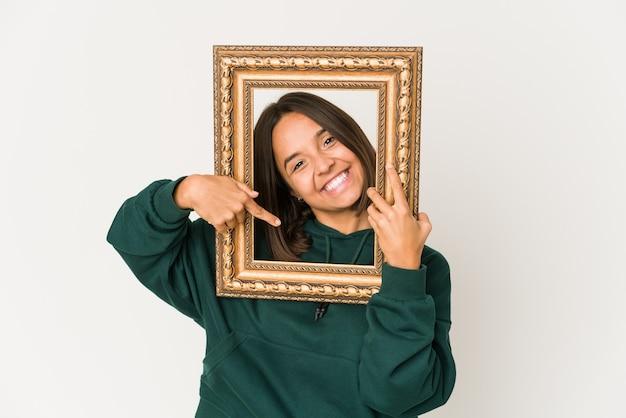 Jovem mulher hispânica segurando um quadro de uma pessoa apontando com a mão para um espaço de cópia de camisa, orgulhosa e confiante