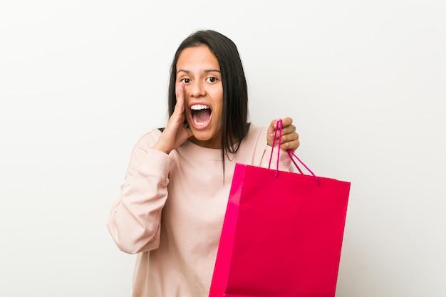 Jovem mulher hispânica, segurando um saco de compras gritando animado para a frente.
