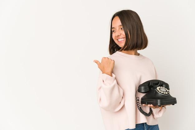 Jovem mulher hispânica segurando um telefone vintage isolado aponta com o dedo polegar, rindo e despreocupada.