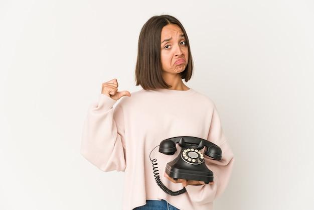 Jovem mulher hispânica segurando um telefone vintage isolado sente-se orgulhosa e autoconfiante, exemplo a seguir.