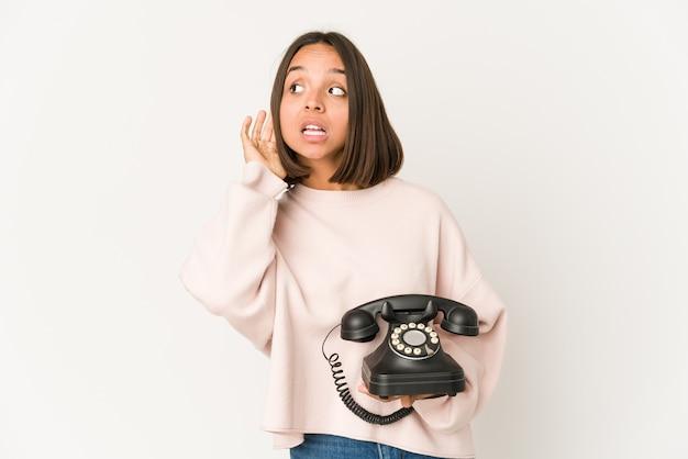 Jovem mulher hispânica segurando um telefone vintage isolado, tentando ouvir uma fofoca.