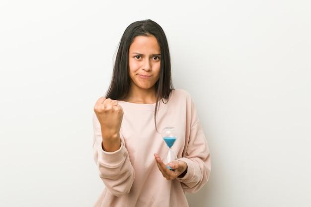 Jovem mulher hispânica segurando uma ampulheta, mostrando o punho para a câmera, expressão facial agressiva.