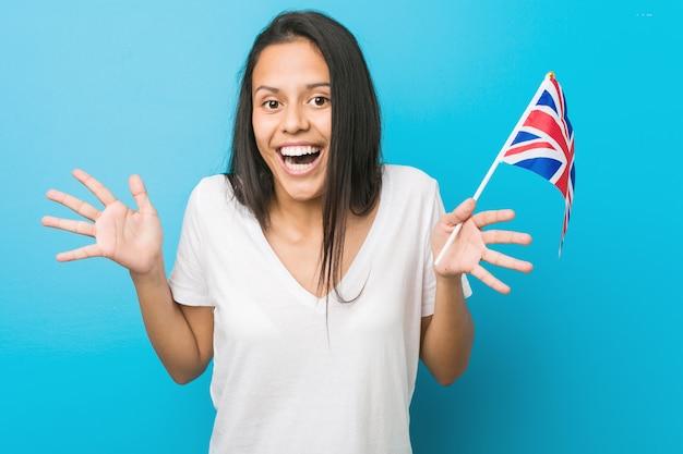 Jovem mulher hispânica, segurando uma bandeira do reino unido comemorando uma vitória ou sucesso