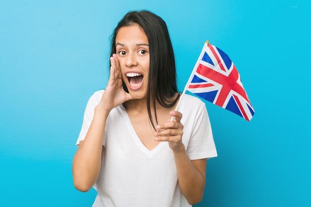 Jovem mulher hispânica segurando uma bandeira do reino unido gritando animado para a frente.