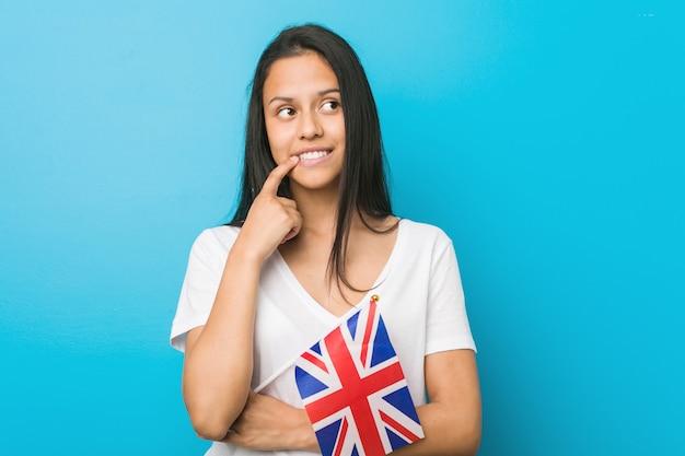 Jovem mulher hispânica, segurando uma bandeira do reino unido relaxado pensando em algo