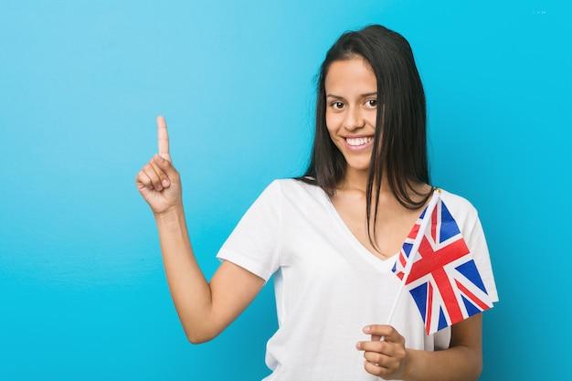 Jovem mulher hispânica segurando uma bandeira do reino unido sorrindo alegremente apontando com o dedo indicador.