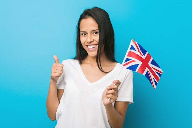 Jovem mulher hispânica segurando uma bandeira do reino unido sorrindo e levantando o polegar