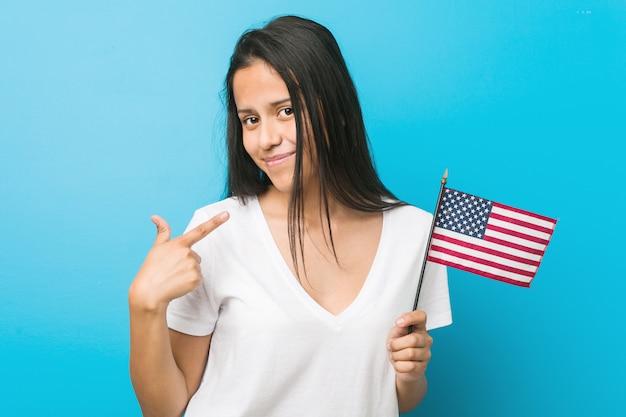 Jovem mulher hispânica, segurando uma bandeira dos estados unidos, apontando com o dedo para você, como se estivesse convidando para se aproximar.