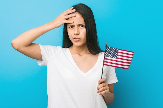 Jovem mulher hispânica segurando uma bandeira dos estados unidos sendo chocada, ela se lembrou de uma reunião importante.